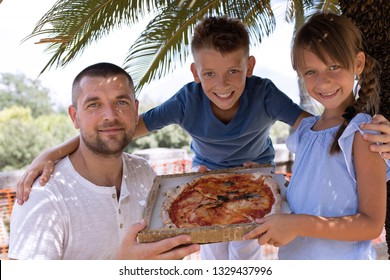 Cute dad with children holding pizza