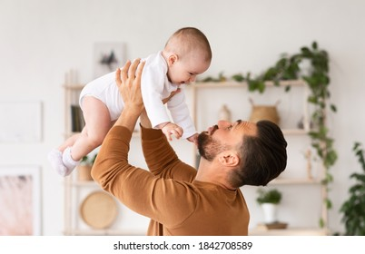Cute Daddy Playing With Newborn Baby Daughter Cuddling And Bonding Holding Little Toddler In Arms Standing At Home. Father's Love, Parenting And Fatherhood Happiness Concept