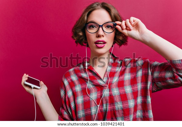 Cute dark-eyed girl in casual clothes listening music in white earphones. Good-looking young lady in glasses posing with interest on claret background in studio.