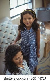 Cute daughter combing mothers hair in living room at home