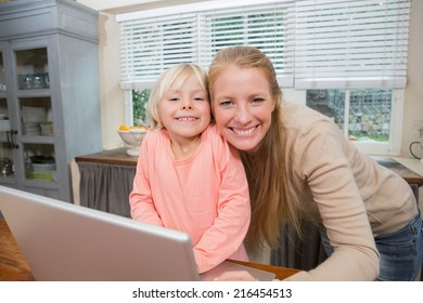 Cute daughter and mother smiling at camera at home in the kitchen