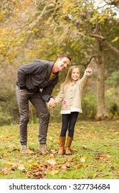 Cute daughter showing something to her father on an autumns day