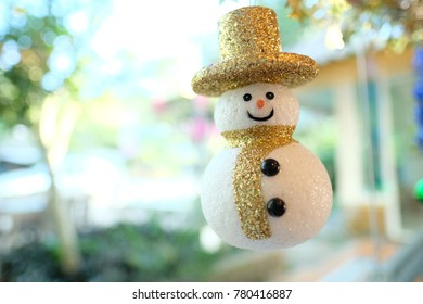 A cute decorative snowman with a  golden hat smailing joyfully by the glass window, Holiday greetings. Christmas and New Year decoration. Seasonal joy. Selective focusing, closeup shot.