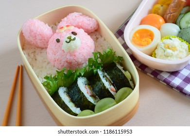 a cute and delicious looking lunch box (bento) consisting of rice ball, sushi roll, boiled egg and the assortment of vegetable