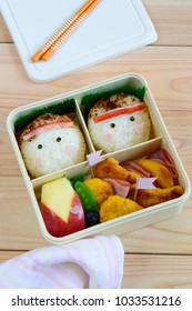 a cute and delicious looking onigiri (rice ball) bento on wooden background