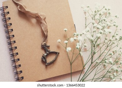 cute diary with kraft cover, vintage pendant in the shape of a horse, white flowers. Concept- childhood happy memories and dreams