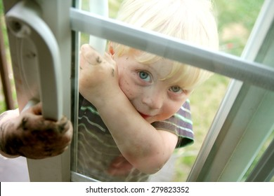 A cute dirty toddler child is smiling as he peeks in the window of a sliding glass door from outside.