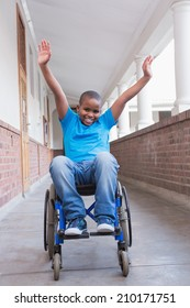 Cute disabled pupil smiling at camera in hall at the elementary school