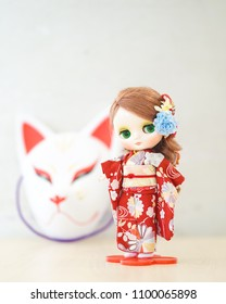 Cute doll in Kimono. A cute doll is dressing up in a red kimono. Kimono is a traditional Japanese garment. The doll is standing in front of a fox traditional mask.