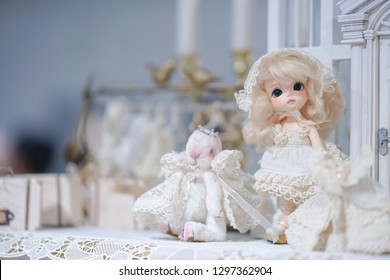 Cute doll on display. Kawaii innocent girl with blond hair in a white lace dress. Lati Yellow doll.