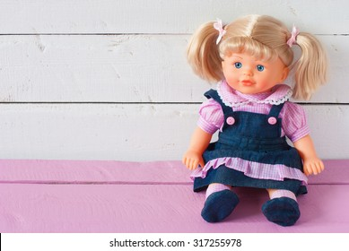 Cute doll sits on the background board