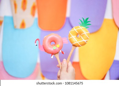 Cute donuts. A lady's hand holding cute flamingo and pineapple sugar glazed doughnuts isolated on colorful background. Summer theme. Fancy food concept for birthday or creative party.