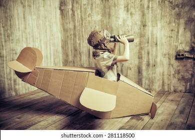 Cute dreamer boy playing with a cardboard airplane. Childhood. Fantasy, imagination. Retro style.