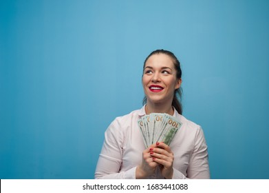 Cute dreamy beautiful woman with a bundle of banknotes dreaming of shopping on a blue background. Holiday shopping concept. Advertising space