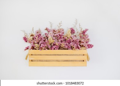 Cute dry flower in wooden basket decorated on white cement wall with copy space for text or image.
