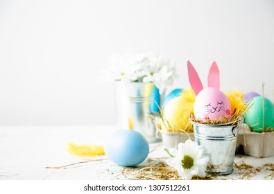 Cute easter background with an egg decorated as a rabbit in a flower pot, daisies and feathers