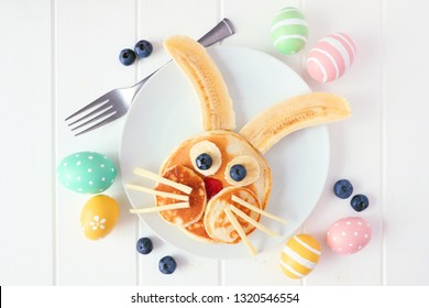 Cute Easter Bunny pancakes on a white plate. Flay lay against a white wood background.
