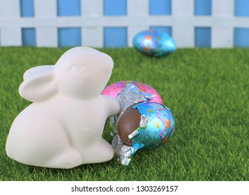 Cute Easter image with ceramic bunny opening chocolate eggs on green grass. A picket fence is in the background