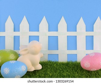 Cute Easter image with green grass, colorful sparkly eggs, a ceramic bunny and a white picket fence with a blue background