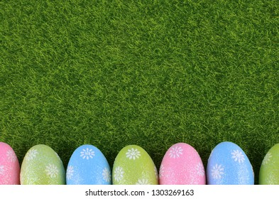 Cute Easter image with green grass as a background and sparkly colored eggs as a lower border. Copy space