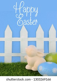 Cute Easter image with green grass, colorful sparkly eggs, a ceramic bunny and a white picket fence with a blue background. Vertical image with message added.
