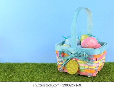 Cute Easter image with green grass and blue sky with colorful easter basket full of sparkly eggs. Copy space