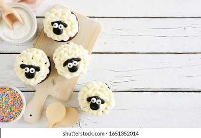 Cute Easter sheep cupcakes. Above view table scene with a white wood background and copy space.