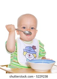 Cute eating child with spoon and plate. Isolated over white