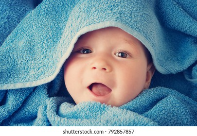 Cute eight month old baby wrapped in a towel