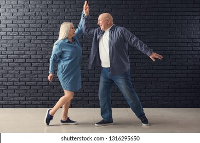 Cute elderly couple dancing against dark brick wall