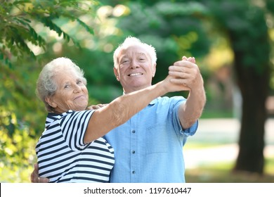 Cute elderly couple dancing outdoors. Time together