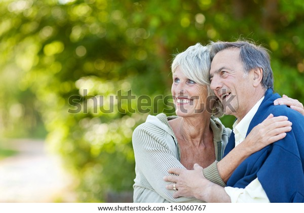 Cute elderly couple holding each other and laughing while looking at something.
