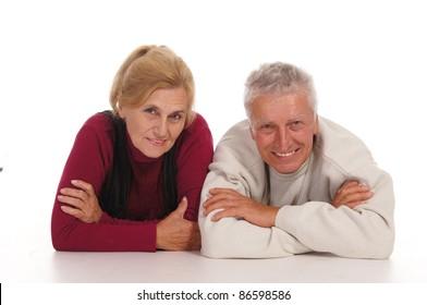 cute elderly couple posing on a white