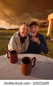 Cute elderly couple at table in a field