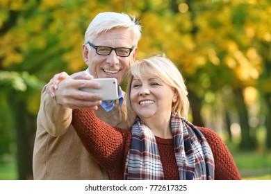 Cute elderly couple taking selfie in autumn park