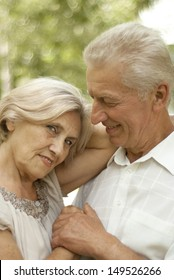 Cute elderly couple went for a walk in the park on a summer day