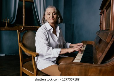 Cute elderly woman playing the piano