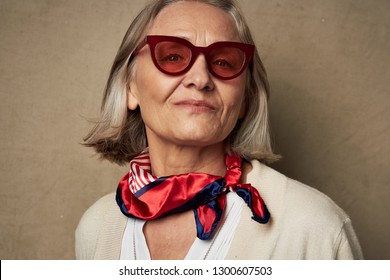 Cute elderly woman in sunglasses with a scarf around her neck on an isolated background