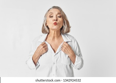 Cute elderly woman in a white shirt holding onto the collar with make-up on the face pulls out lips gray background