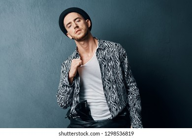 Cute elegant man with a brutal look in a black hat on his head in glasses black and white shirts on a dark isolated background street style