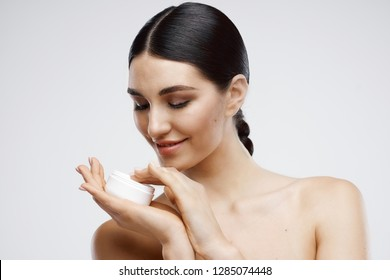 Cute elegant woman with bare shoulders holds cream in hand