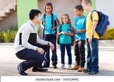 cute elementary pupils outside classroom talking to teacher