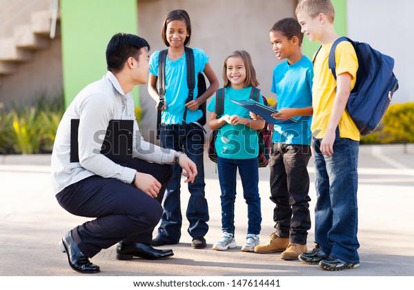 cute elementary pupils outside classroom talking to teacher