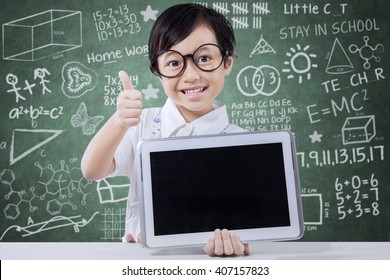 Cute elementary school student showing thumb up and a digital tablet screen in the classroom