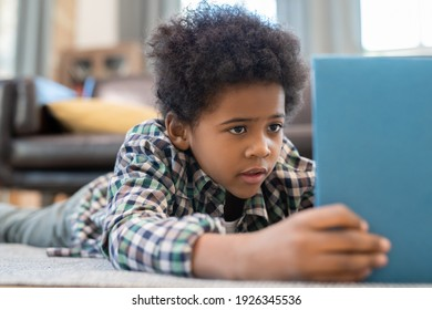 Cute elementary schoolboy with digital tablet lying on the floor against black leather couch in living-room and watching curious online video