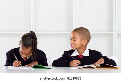 cute elementary schoolboy peeking on classmate's answer