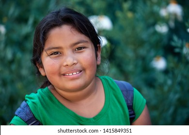 Cute elementary student with backpack in front of green flowers with a positive attitude and natural look.