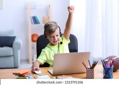 Cute emotionaler Junge, der zu Hause auf dem Laptop Videospiel spielt