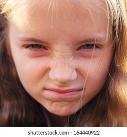 cute emotional little girl outdoors closeup