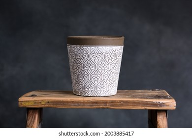 Cute empty indoor plant pot on top of a vintage wooden step ladder in front of a dark turquoise textured painted background